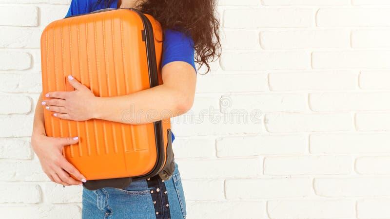 Mujer feliz que abraza su maleta anaranjada Aislado en blanco, espacio de la copia La muchacha casual está lista para viajar Sueñ imágenes de archivo libres de regalías