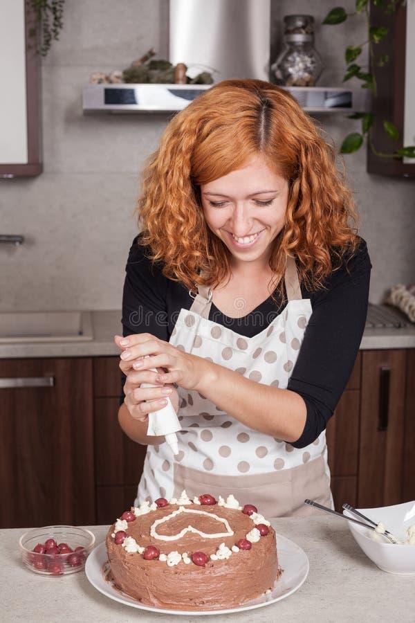 Mujer feliz que adorna la torta en casa imagen de archivo