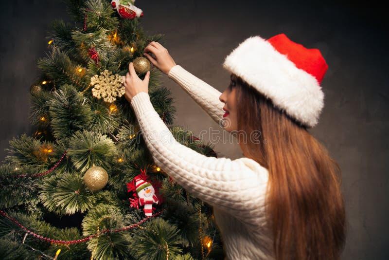 Mujer feliz que adorna un árbol de navidad foto de archivo