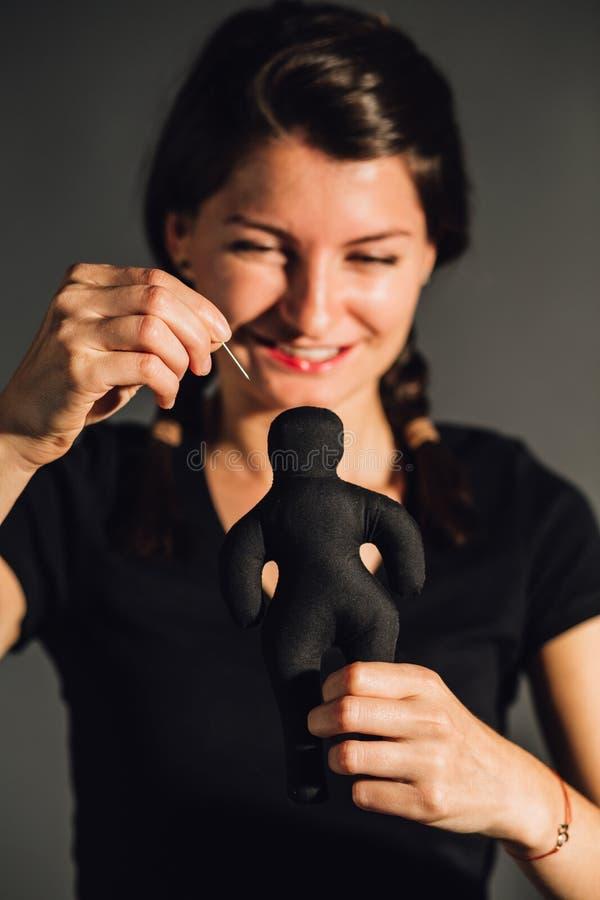 Mujer feliz que apuñala una muñeca fotografía de archivo libre de regalías