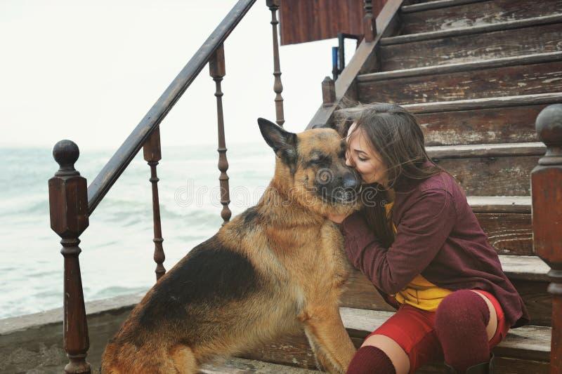Mujer feliz que besa su perro de pastor alemán foto de archivo