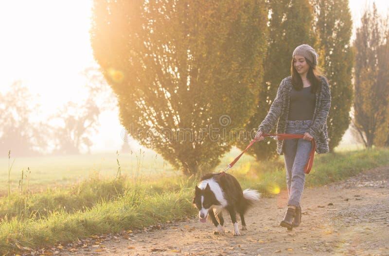 Mujer feliz que camina con su border collie foto de archivo libre de regalías