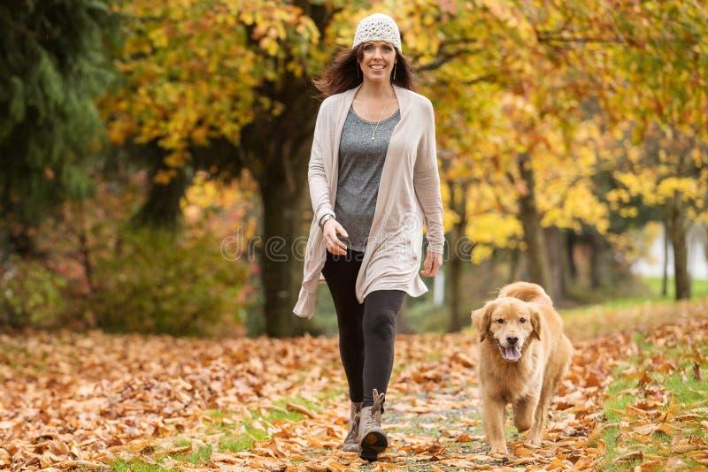 Mujer feliz que camina su perro del golden retriever en un parque con caída imagen de archivo