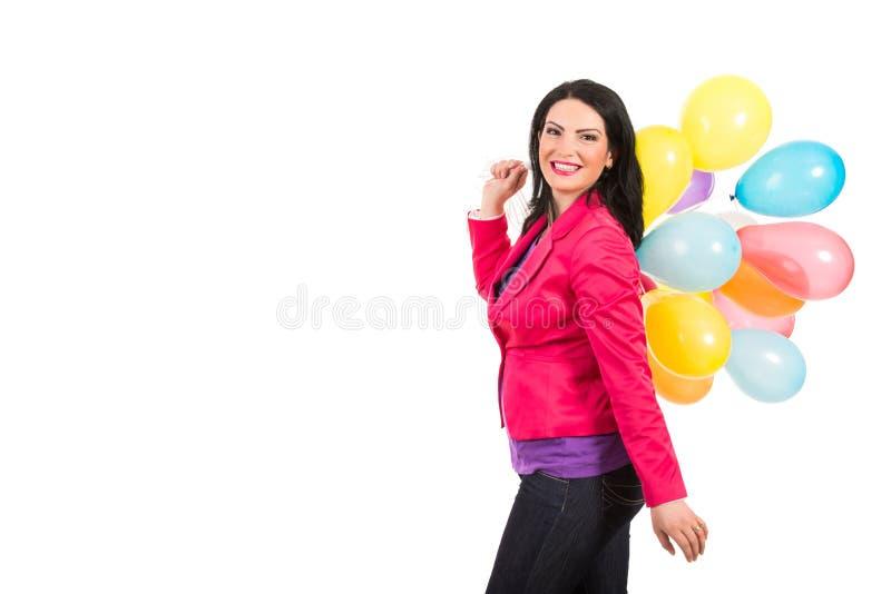 Mujer feliz que camina y que sostiene los globos fotografía de archivo libre de regalías