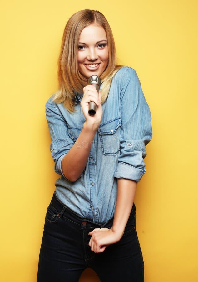 Mujer feliz que canta en micrófono sobre fondo amarillo imagen de archivo libre de regalías