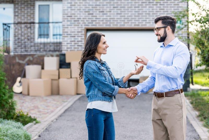 mujer feliz que compra la nueva casa y que toma llaves imagenes de archivo