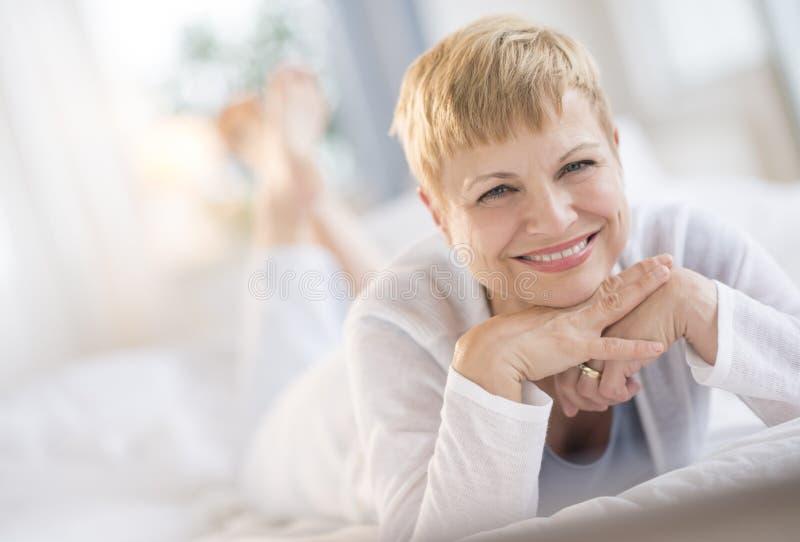 Mujer feliz que descansa a Chin On Hands While Lying en cama fotos de archivo libres de regalías