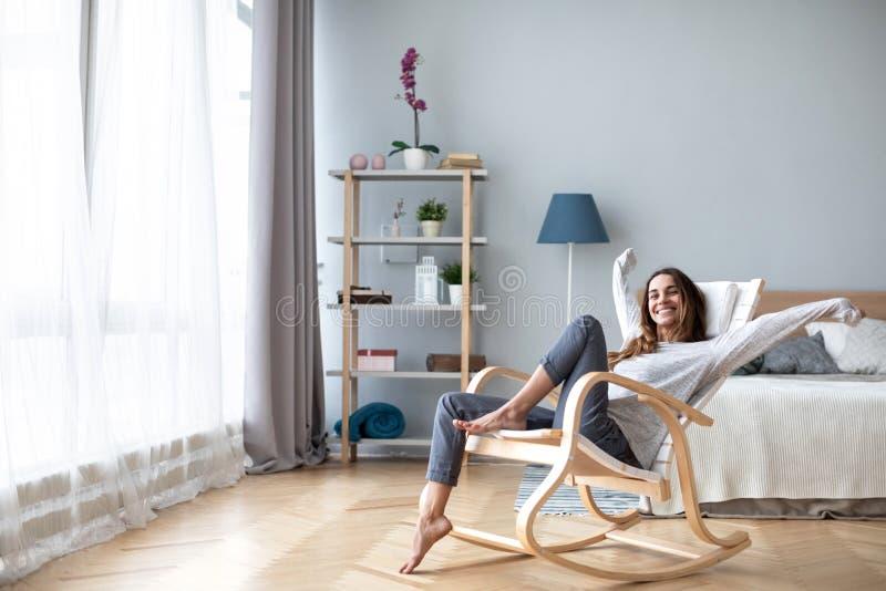 Mujer feliz que descansa comfortablemente sentarse en silla moderna en la sala de estar en casa foto de archivo libre de regalías