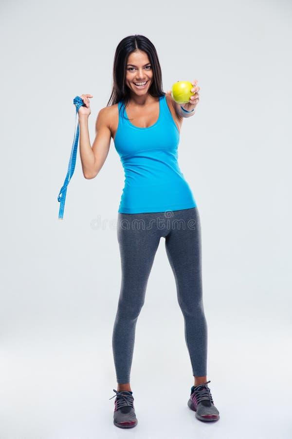 Mujer feliz que detiene la manzana y a la cinta métrica fotografía de archivo libre de regalías