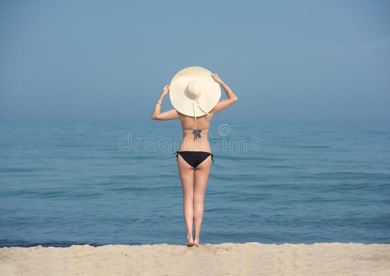 Mujer feliz que disfruta de la relajación de la playa alegre en verano por el agua azul imagen de archivo libre de regalías