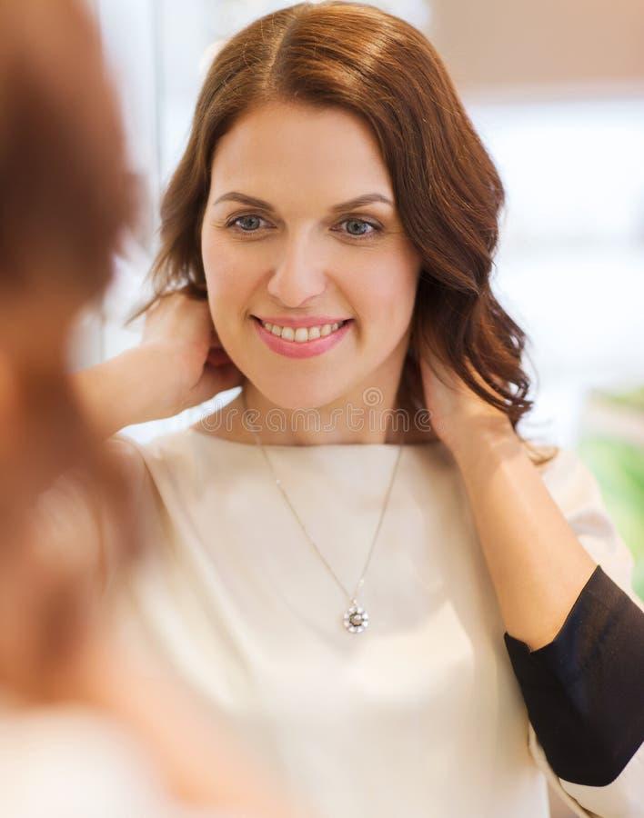 Mujer feliz que elige el colgante en la joyería imagen de archivo libre de regalías