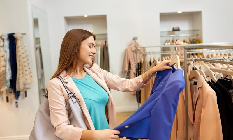 Mujer feliz que elige la ropa en la tienda de ropa foto de archivo libre de regalías