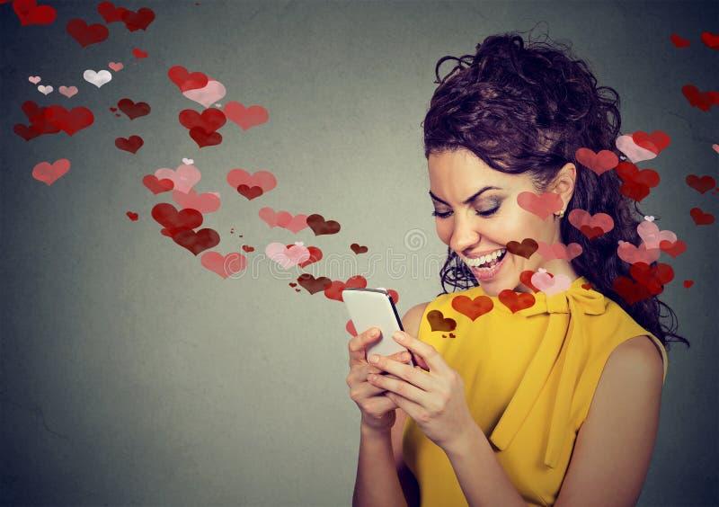 Mujer feliz que envía el mensaje de texto del amor en el teléfono móvil fotografía de archivo libre de regalías
