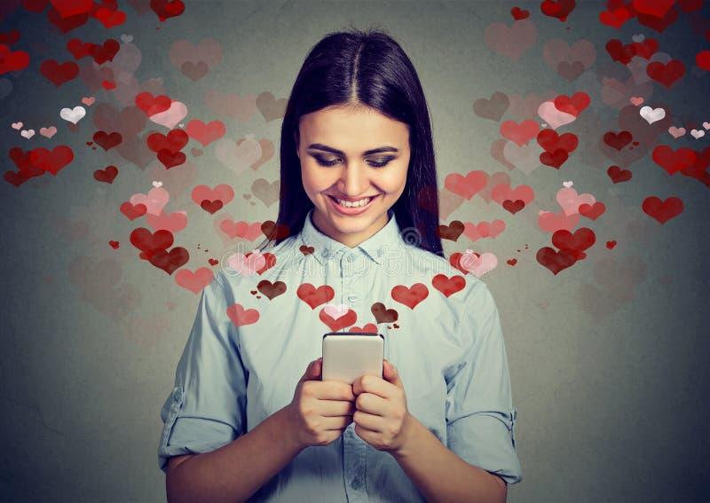 Mujer feliz que envía el mensaje del amor en los corazones del teléfono móvil que se van volando foto de archivo libre de regalías