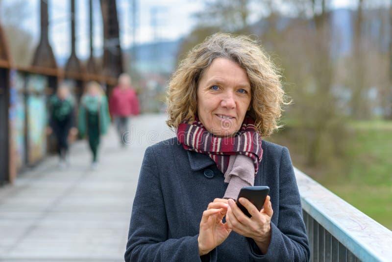 Mujer feliz que envía un mensaje de texto fotografía de archivo libre de regalías