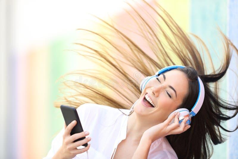 Mujer feliz que escucha el baile de la música en una calle colorida fotos de archivo