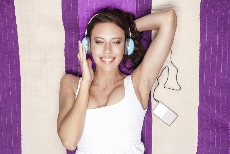 Mujer feliz que escucha la música con reproductor Mp3 usando los auriculares mientras que miente en la manta de la comida campest imagen de archivo
