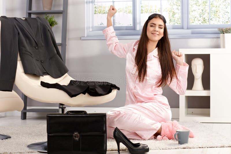 Mujer feliz que estira en pijama foto de archivo