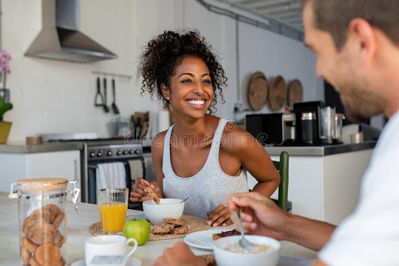 Mujer feliz que goza del desayuno con el hombre en casa fotografía de archivo libre de regalías