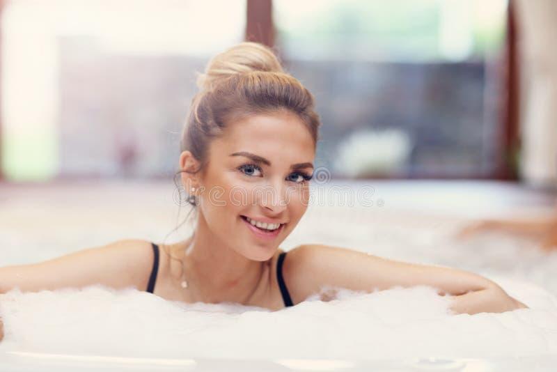 Mujer feliz que goza del Jacuzzi en balneario del hotel fotos de archivo libres de regalías