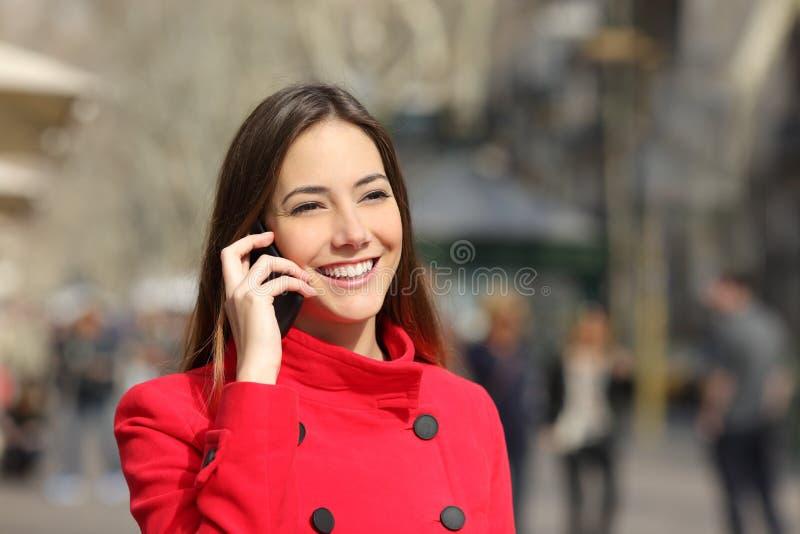 Mujer feliz que habla en el teléfono en invierno en la calle fotos de archivo