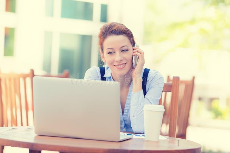Mujer feliz que habla en el teléfono móvil que trabaja en el ordenador portátil del ordenador fotografía de archivo libre de regalías