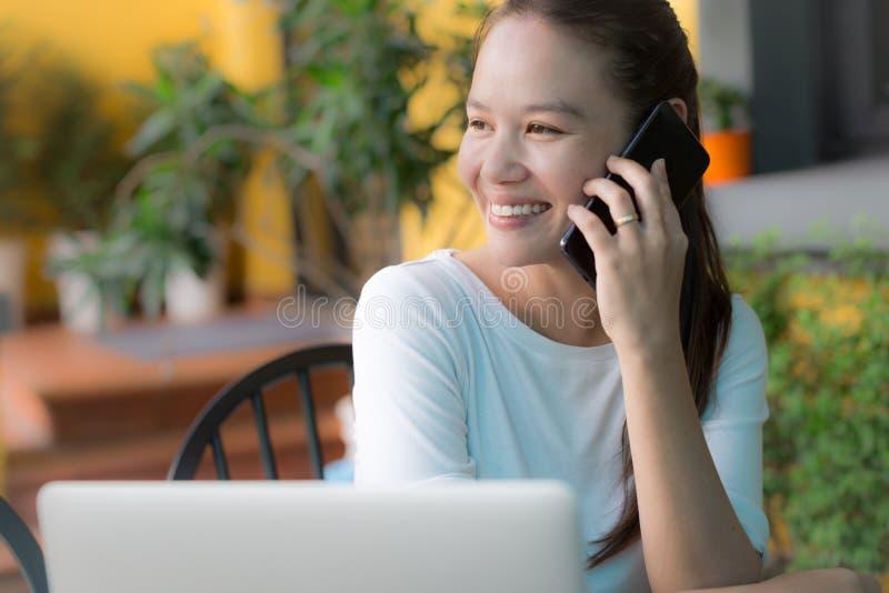 Mujer feliz que habla en su teléfono en casa Comunicaciones empresariales fotos de archivo libres de regalías