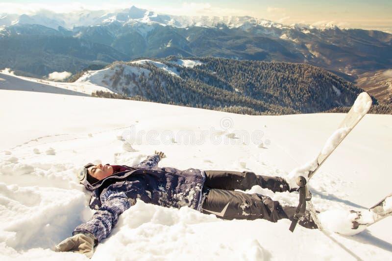 Mujer feliz que hace ángel de la nieve en la nieve foto de archivo libre de regalías