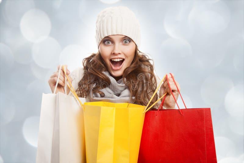 Mujer feliz que hace compras que sostiene bolsos Ventas del invierno fotos de archivo