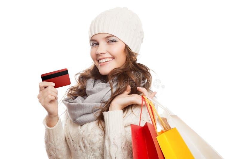 Mujer feliz que hace compras que sostiene bolsos y la tarjeta de crédito Ventas del invierno imágenes de archivo libres de regalías