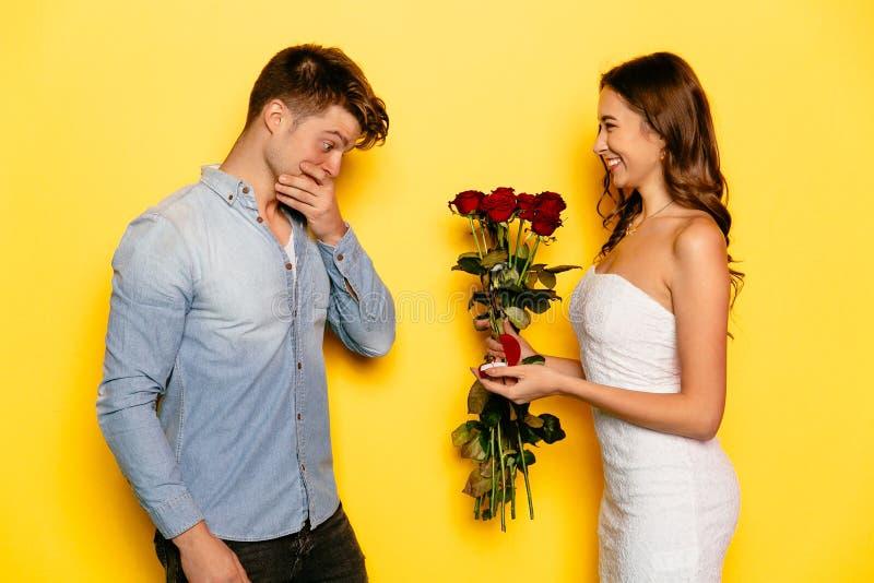 Mujer feliz que hace propuesta de matrimonio a su novio imagenes de archivo
