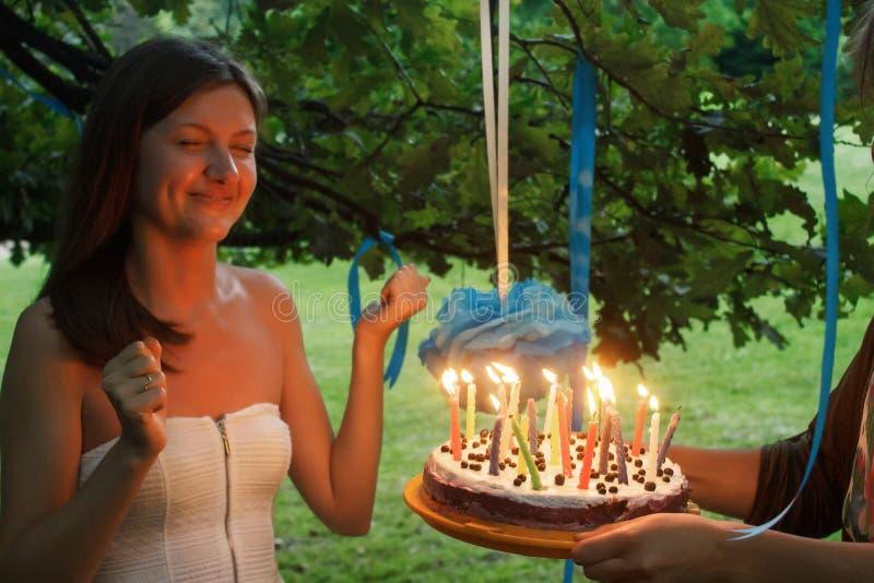 Mujer feliz que hace un deseo y que sopla velas en la torta en su bri imágenes de archivo libres de regalías
