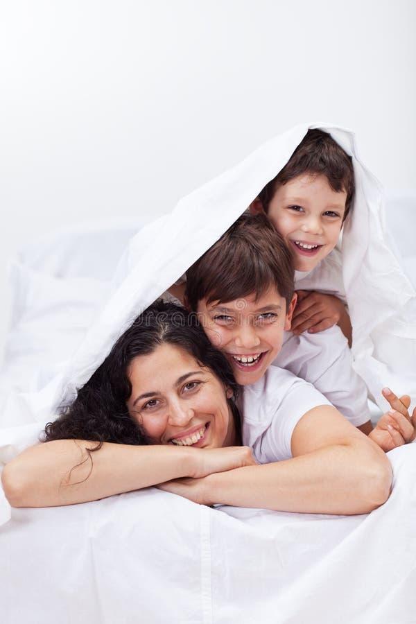 Mujer feliz que juega con sus niños imagenes de archivo