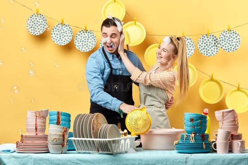 Mujer feliz que lava la cara de su marido con el líquido del lavaplatos imagenes de archivo