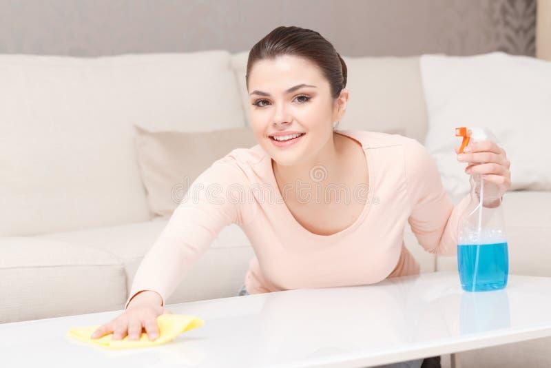 Mujer feliz que limpia la tabla blanca fotografía de archivo libre de regalías