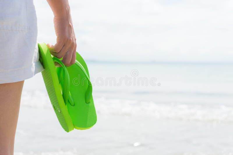 Mujer feliz que lleva a cabo chancleta verde en la playa arenosa para el verano fotos de archivo libres de regalías