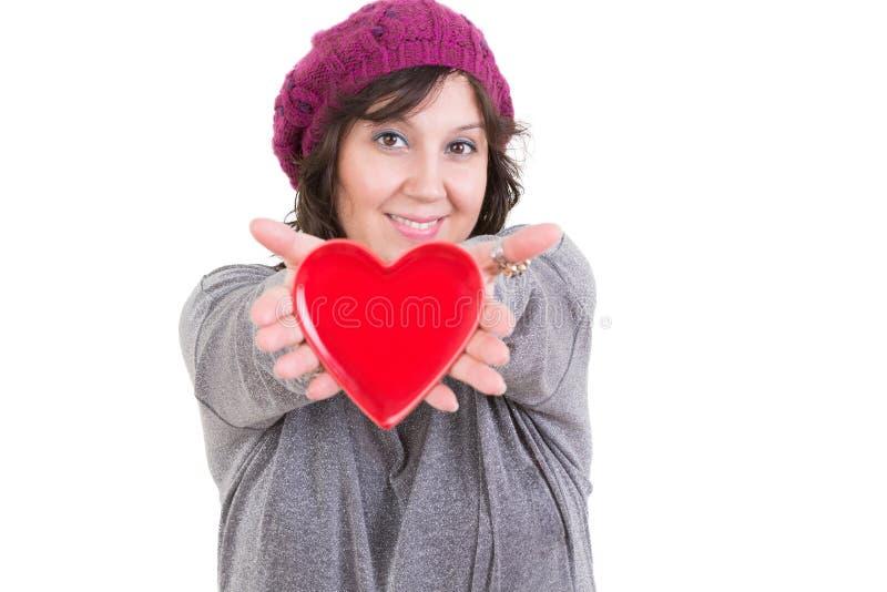 Mujer feliz que lleva a cabo hacia fuera un corazón rojo de las tarjetas del día de San Valentín imagen de archivo libre de regalías