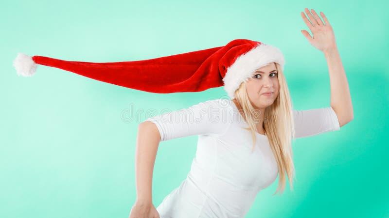 Mujer feliz que lleva el funcionamiento del sombrero de Santa Claus foto de archivo libre de regalías