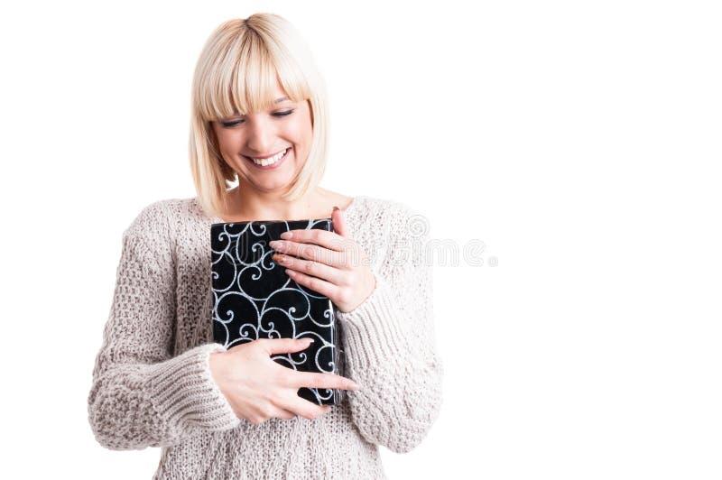 Mujer feliz que lleva el suéter caliente que lleva a cabo un presente imagen de archivo libre de regalías