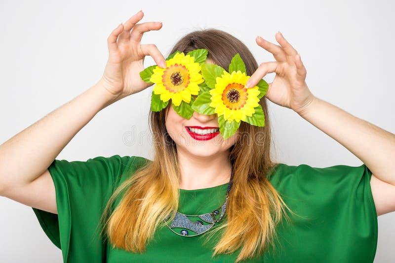Mujer feliz que lleva en el vestido verde que sostiene dos flores cerca de sus ojos imagenes de archivo