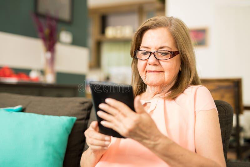 Mujer feliz que lleva sus vidrios para leer imagen de archivo libre de regalías