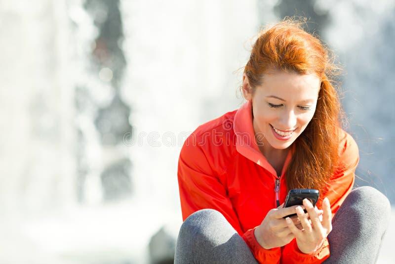 Mujer feliz que manda un SMS en el teléfono fotos de archivo libres de regalías