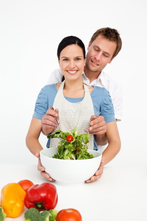 Mujer feliz que mezcla una ensalada con su novio foto de archivo libre de regalías