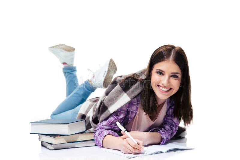 Mujer feliz que miente en el piso y que escribe en cuaderno imágenes de archivo libres de regalías