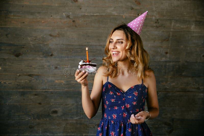 Mujer feliz que mira el pedazo de torta de chocolate con la vela fotos de archivo