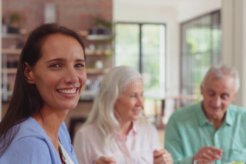 Mujer feliz que mira la cámara mientras que teniendo comida en la mesa de comedor fotografía de archivo