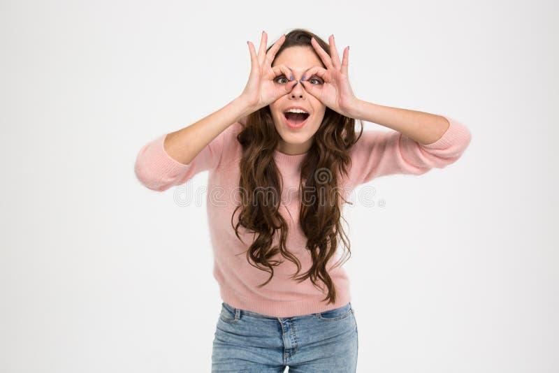 Mujer feliz que mira la cámara a través de los fingeres imagen de archivo