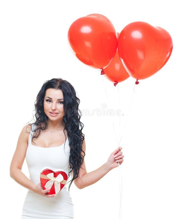 Mujer feliz que mira su en forma de corazón rojo de la caja de regalo para el día del ` s de la tarjeta del día de San Valentín T fotografía de archivo