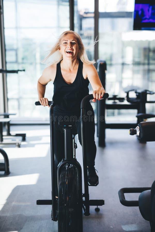 Mujer feliz que monta una bici del aire en el gimnasio imagen de archivo libre de regalías
