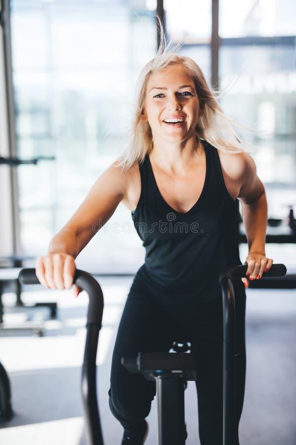 Mujer feliz que monta una bicicleta en el gimnasio imagen de archivo